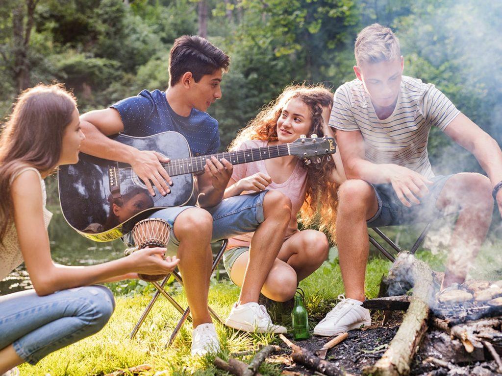 Jungendliche beim Campen am Lagerfeuer