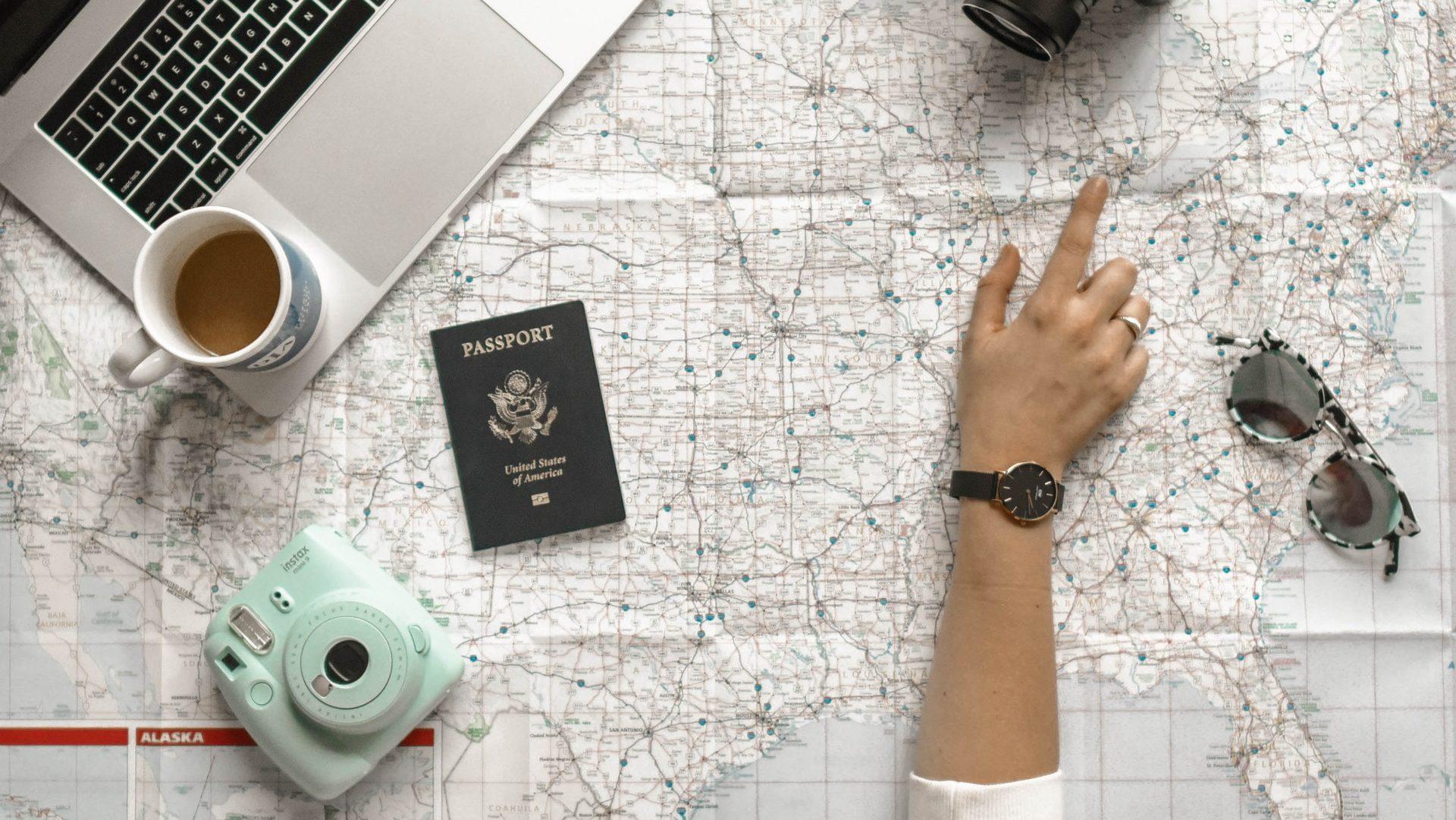 Reiseplanung mit Reiseutensilien, unter anderen Notebook, Reisepass, Kamera und Sonnenbrille