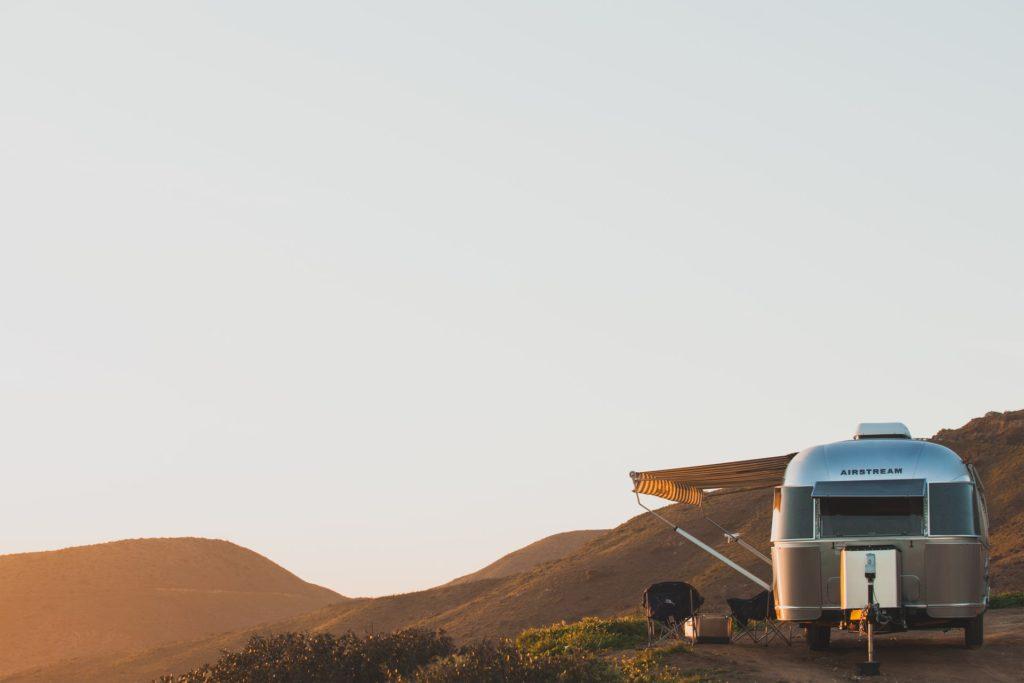 Camper mit offener Markise im Sonnenuntergang